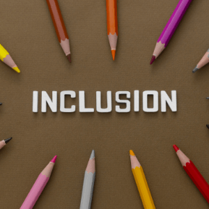 """The word """"inclusion"""" is written in white lettering against a brown background. 10 colored pencils of various colors and framing the word along the edge of the photo."""