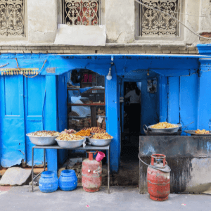 A blue store front kitchen in Nepal with two tables outside of it. Food in serving platters is spread across the tables.