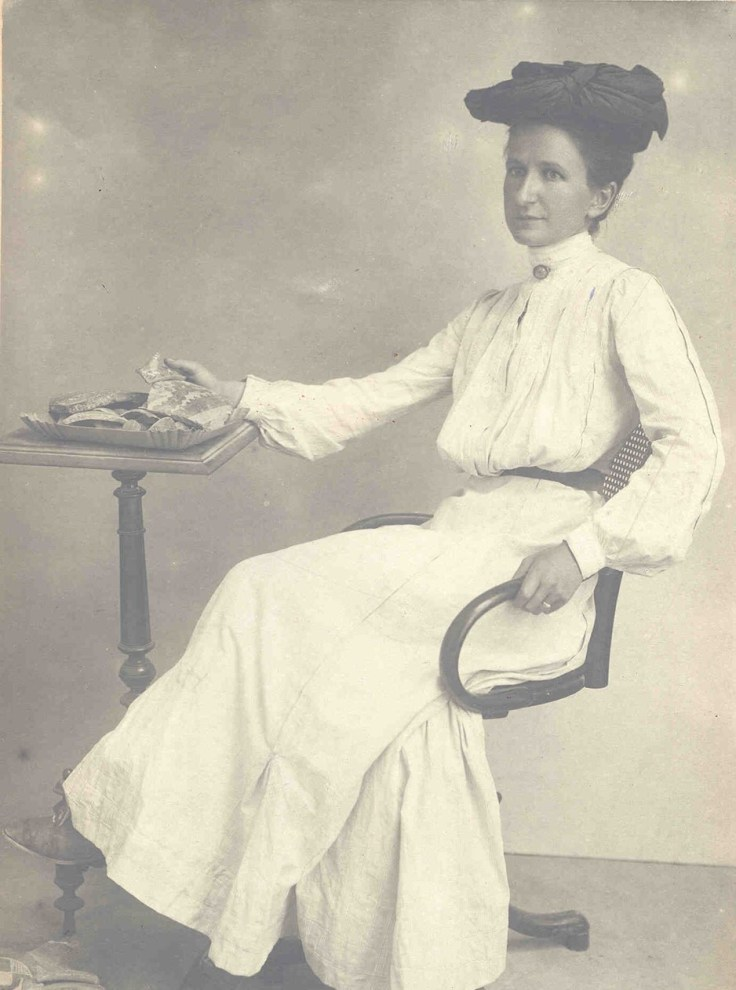 Harriet Boyd Hawes sitting at a table with a tray of what appears to be pottery sherds in front of her. The photo is black and white.