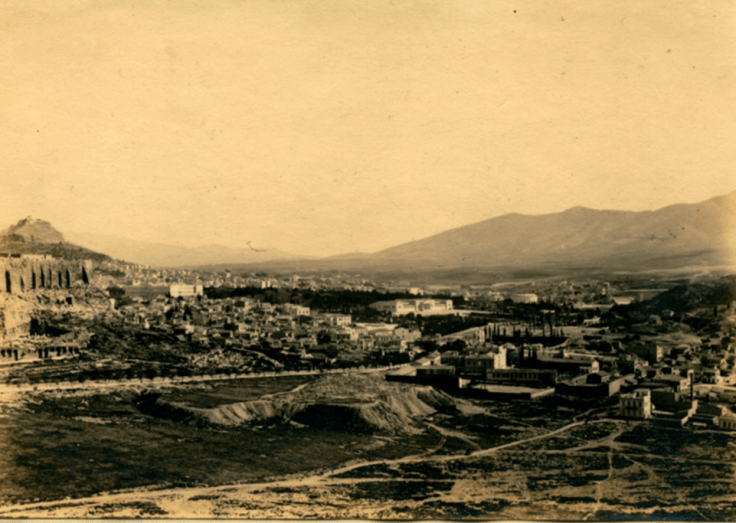 Photo of Athens in 1897-1898, possibly taken by Harriet Boyd Hawes and certainly taken during her time at the American School of Classical Studies there. The photo shows mountains in the background, the city in the midground, and bare earth in the foreground. The photo is in sepia tones.