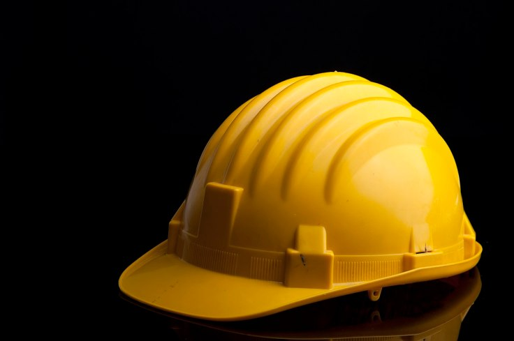 A yellow hardhat on a black background.