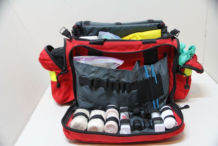 A red first aid kit. The kit is unzipped and you can see that it contains a variety of medical items and is well organized.