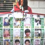 Woman holds up pictures of missing children - Wuhan, Hubei province, China