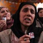 Women crying and holding photographs of loved ones during hunger strike.