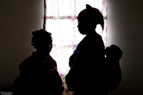 Silhouette of two pregnant victims of sexual abuse. One is carry baby on her back.
