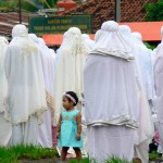 A little girl praying with women dressed in burkas.