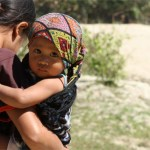 Indonesian child being carried by her mother