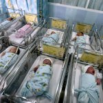 New borns seen through a hospital nursery window