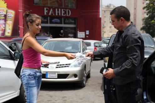 Woman hands out brochures for ABAAD in Beirut, Lebanon