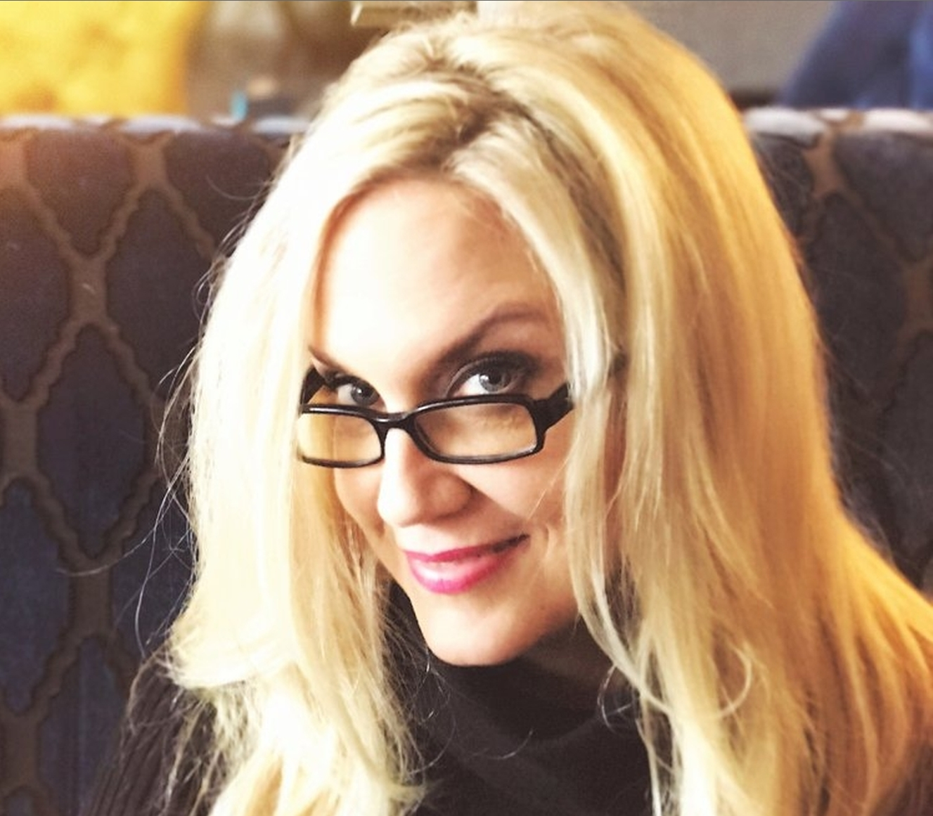 Photo of Brenda Romero from the shoulders up, looking over the top edge of her glasses and smiling.