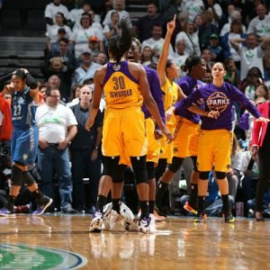 Sparks players continue to exalt while Lynx forward Maya Moore, left, absorbs the loss. Photo by David Sherman/NBAE Getty Images.