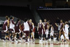 Texas A&M bench players greet the starters as they come off the floor. Photo by Maria Noble/WomensHoopsWorld.