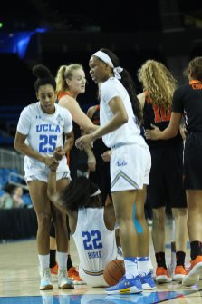 Kennedy Burke is helped to her feet after being fouled. Photo by Maria Noble/WomensHoopsWorld.