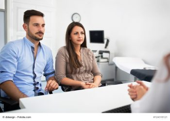 Doctor with patients at clinic, consulting about pregnancy