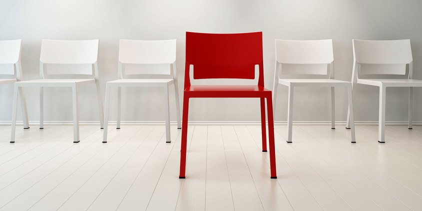 single red chair amongst white chairs