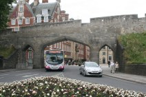 city wall, bus and cars coming under it.