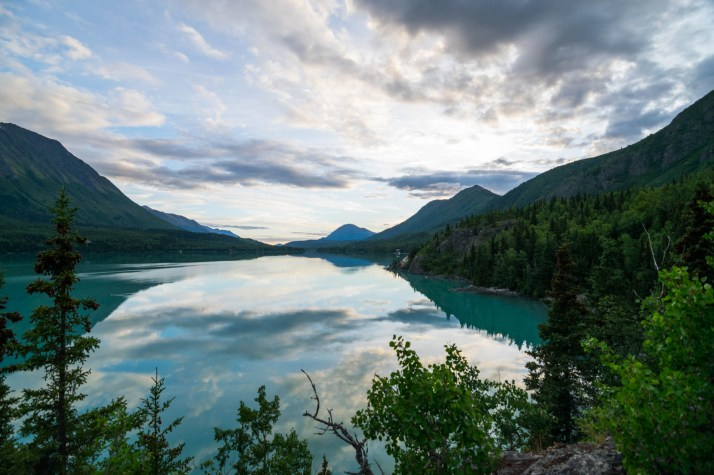 Kenai Lake, a turquoise glacial lake refects a beautiful blue and partly cloudy sky. The lake is surrounded by mountains and forests. Located in Cooper Landing, Alaska