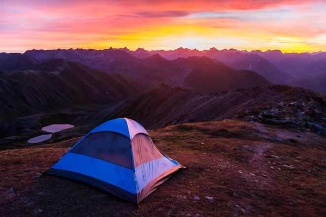 The sun rises in a spectacular burst of colors over a horizon of endless mountain peaks. Campers in a blue tent with bug spray marks are well positioned for the view on a mountain ridgeline above a couple of alpine lakes.
