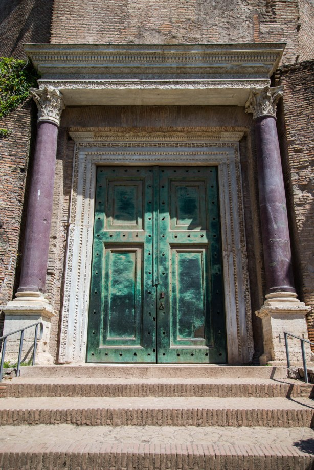 An ancient green door is seen among classical architecture in the ruins of the roman forum.