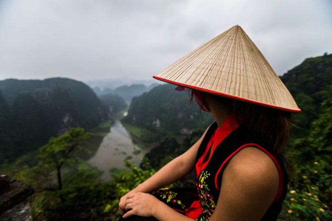 A young asian woman wearing a pointy conical straw hat overlooks foggy mountains from a vantage point near Tam Coc in vietnam. Her dress is black and red with flowers.