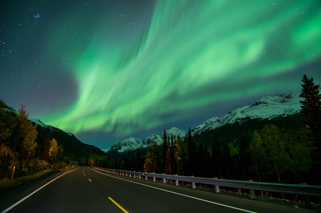 Bright green northern lights burst over a forest road in alaska. A street light illuminates the road. Stars shine overhead.
