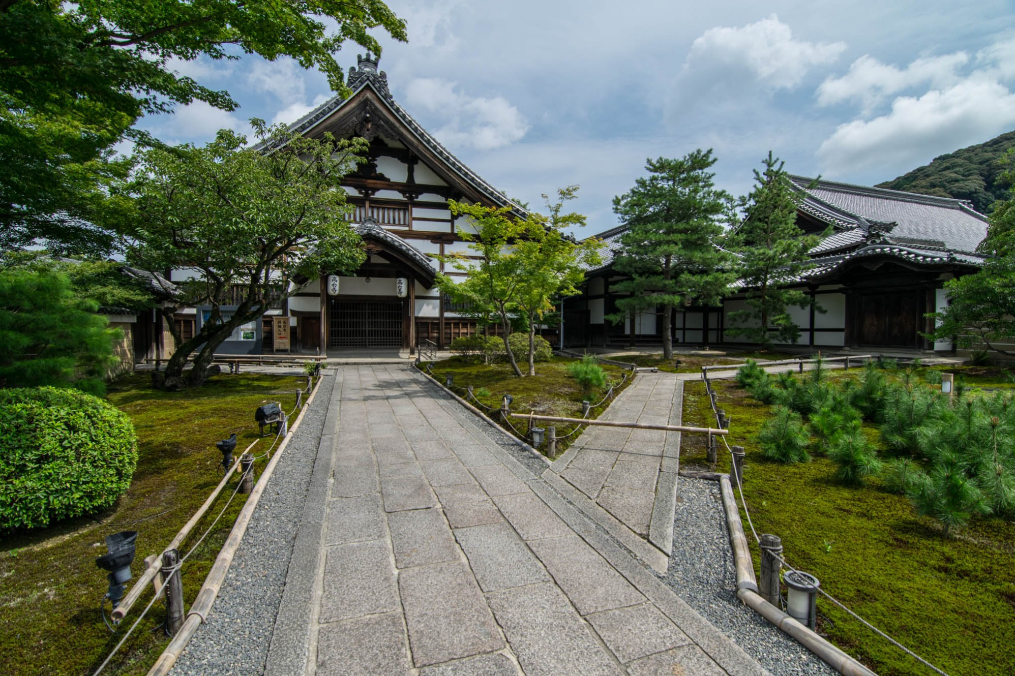 A brick pathway forks towards two two traditional Japanese temples in green garden.