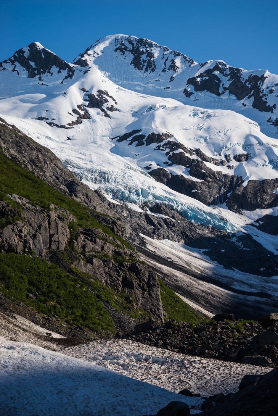 The blue ice of Alaska's Byron glacier cascades down a mountain top on a summer day. The aftermath of an avalanche is seen in the foreground.