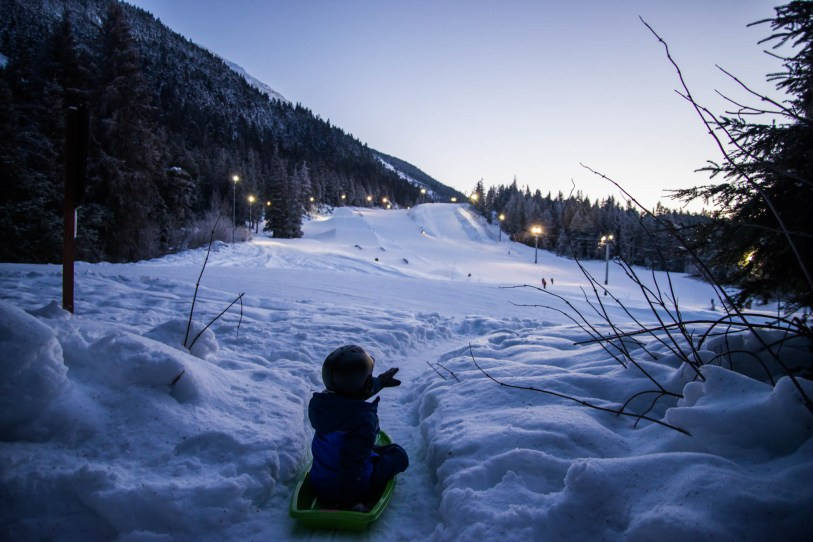 A young boy wearing a helmet points towards ski slopes while sledding down a snowy trail during twilight in Alyeska Alaska.