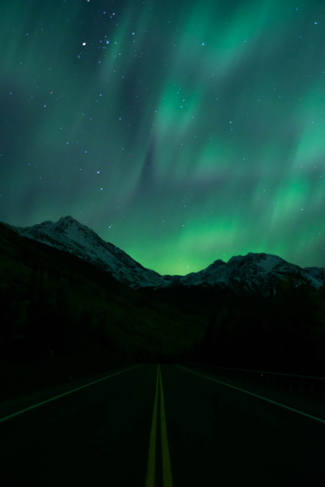 Green soft aurora shines among stars. Double yellow road lines are seen centered as the road approaches snow capped mountains in an Alaskan forest.