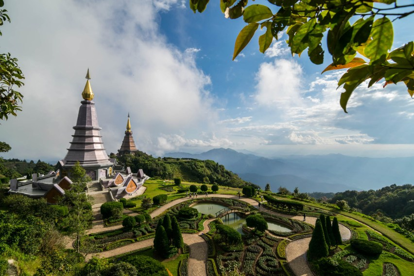 Two futuristic temples are seen on the top of Thailand's highest mountain, Doi Inthanon. A beautiful garden is seen around the temple grounds. Vertical profile.