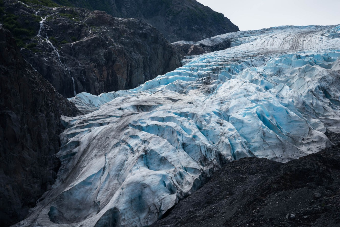 A blue and white crevasse filled glacier descends down a rocky mountain. A small waterfall