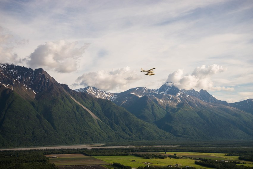 A float plane flys on a perfect day over Palmer Alaska's farmlands and along side forested mountains. The sky is bright and partly cloudy. There is a stong sense of freedom.