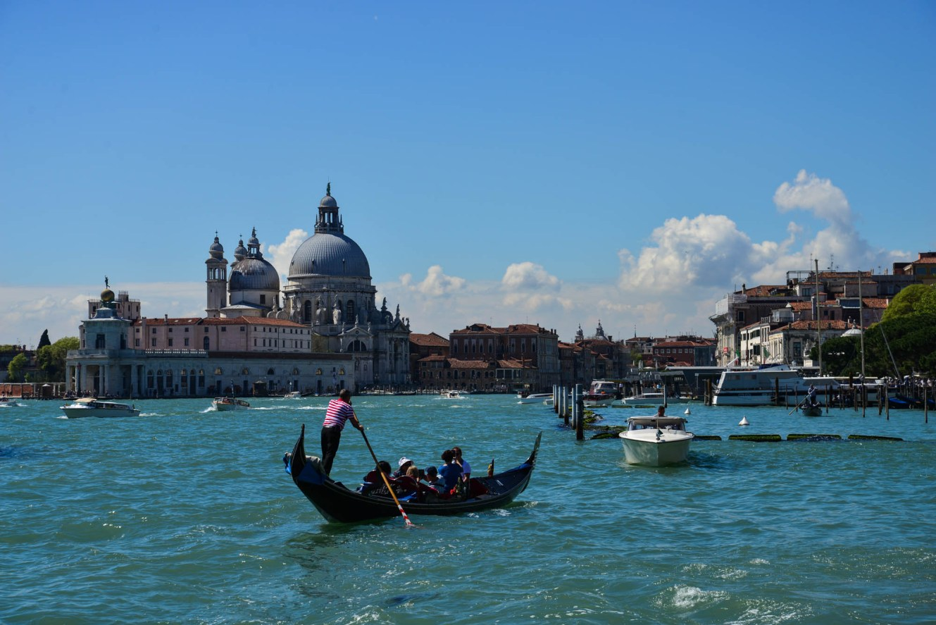 A gondolier wearing the traditional Waldo red and white stripes rows a family in a gondola along Venice's main waterway. A large domed church sits in the background.