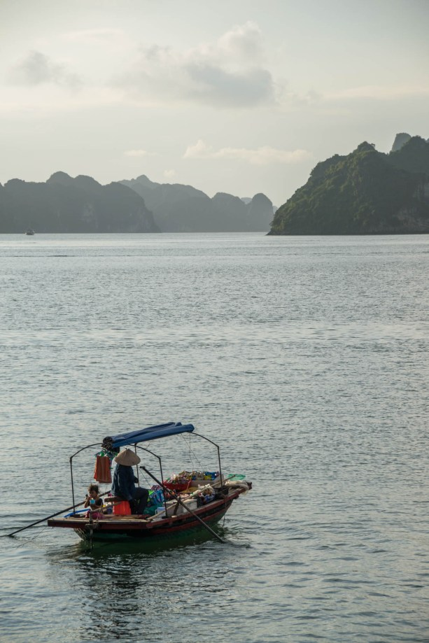 A little girl eats from a cup as her mother rows a small boat trying to sell snacks to tourists in the vast waters of Vietnam's Halong bay. Her little boat is certainly makeshift as she sits a top a bucket and uses rope to hold the boat together.