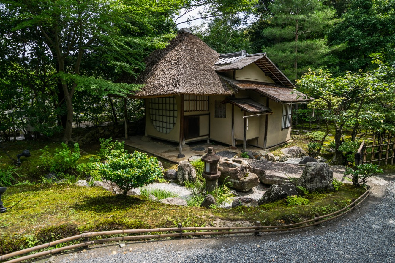 A little wooden buillding with a straw roof sits quietly in a japanese zen garden in Kyoto Japan.