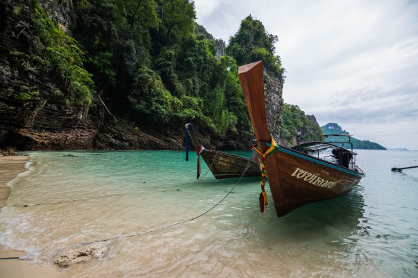 Two wooden longtail boats are anchored to a secluded sandy beach on the outskirts Railay beach in Thailand.
