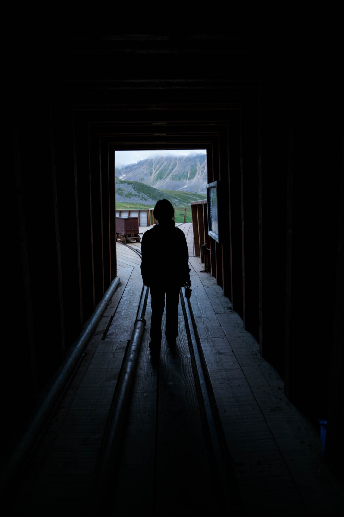 A young woman explores the entrance to an abandoned gold mine in alaska. Her silhouette is seen among a backdrop of mountains and rail tracks