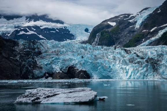 Surprise glacier descends from the clouds , past the mountains and into the ocean. An iceburg floats in the foreground and a waterfall cascades in the background. Located near prince william sound Alaska