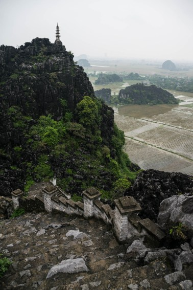 A look down from Hang Mua overlook near Tam Coc Vietnam . An old stone staircase decends from a mountain top pagoda to a backdrop of rural rice paddies .