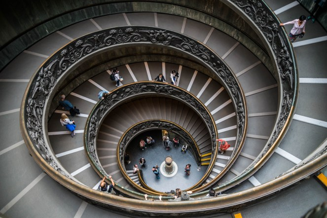 People descending the Louvre's spiral staircase.