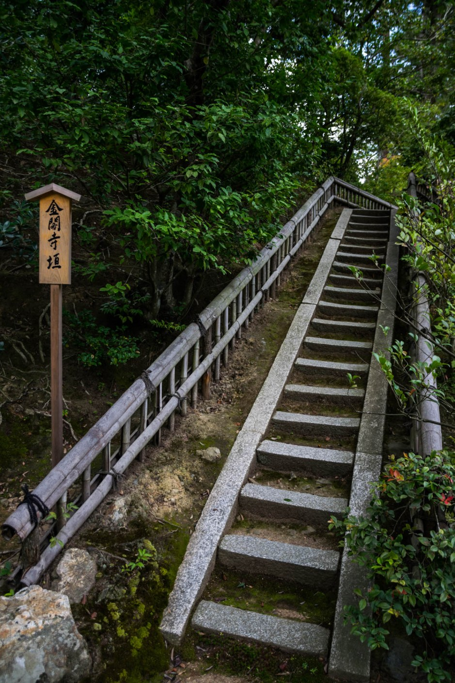 Stone stairs with a bamboo handrail in a japanese garden lead to the unknown. A wooden sign with traditional japanese characters is posted.