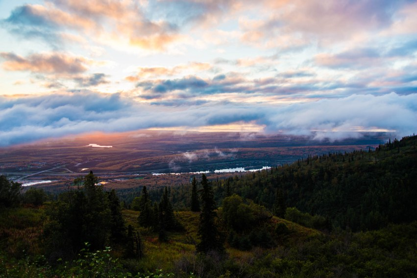 A colorful sunset is seen among low hanging clounds and the Chugach forest neat Eagle River Alaska. The Seward highway is seen down below from the vantage point of a mountian hill. The forest is green and lively.