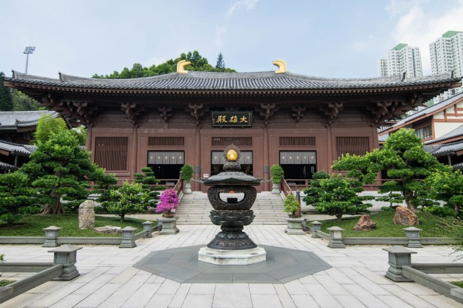 A traditional chinese temple is seen towering above its empty zen inspired courtyard