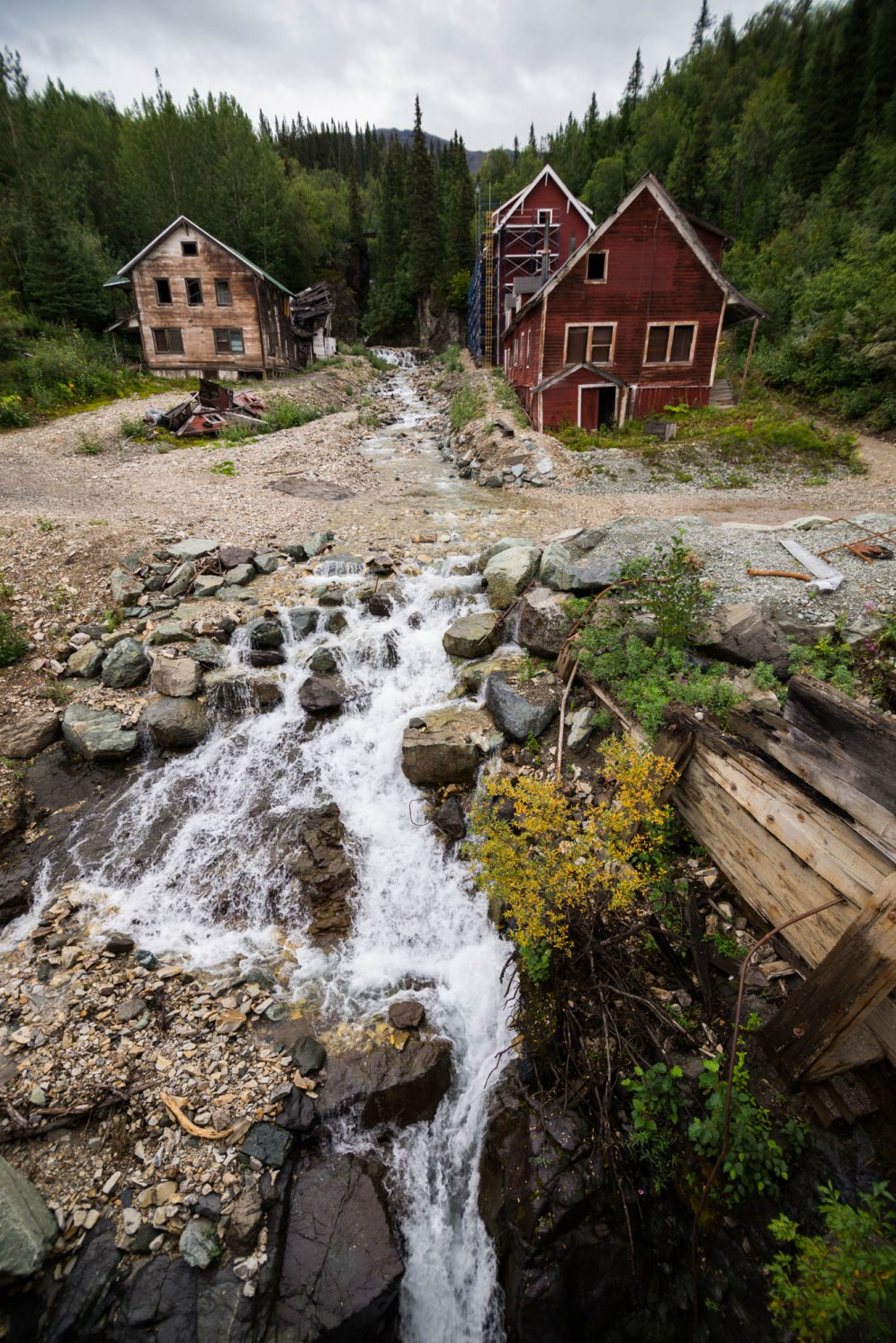 Two old abandoned cabins sit on both sides of a small stream flowing through gravel and rocks. Vertical orientation.