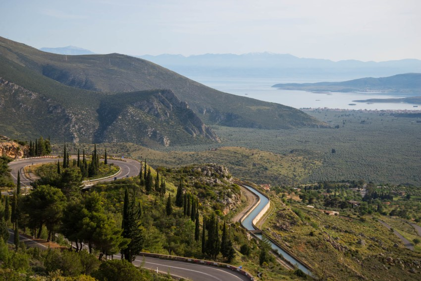 A winding mountian road lined with pine trees makes its way down a valley to the Gulf of Corinth in Greece.