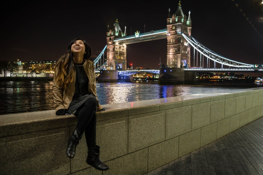 A young woman smiles and looks toward the sky as a street light shines on her face. She sits on a brickwall along the River Thames with London's Tower bridge in the background