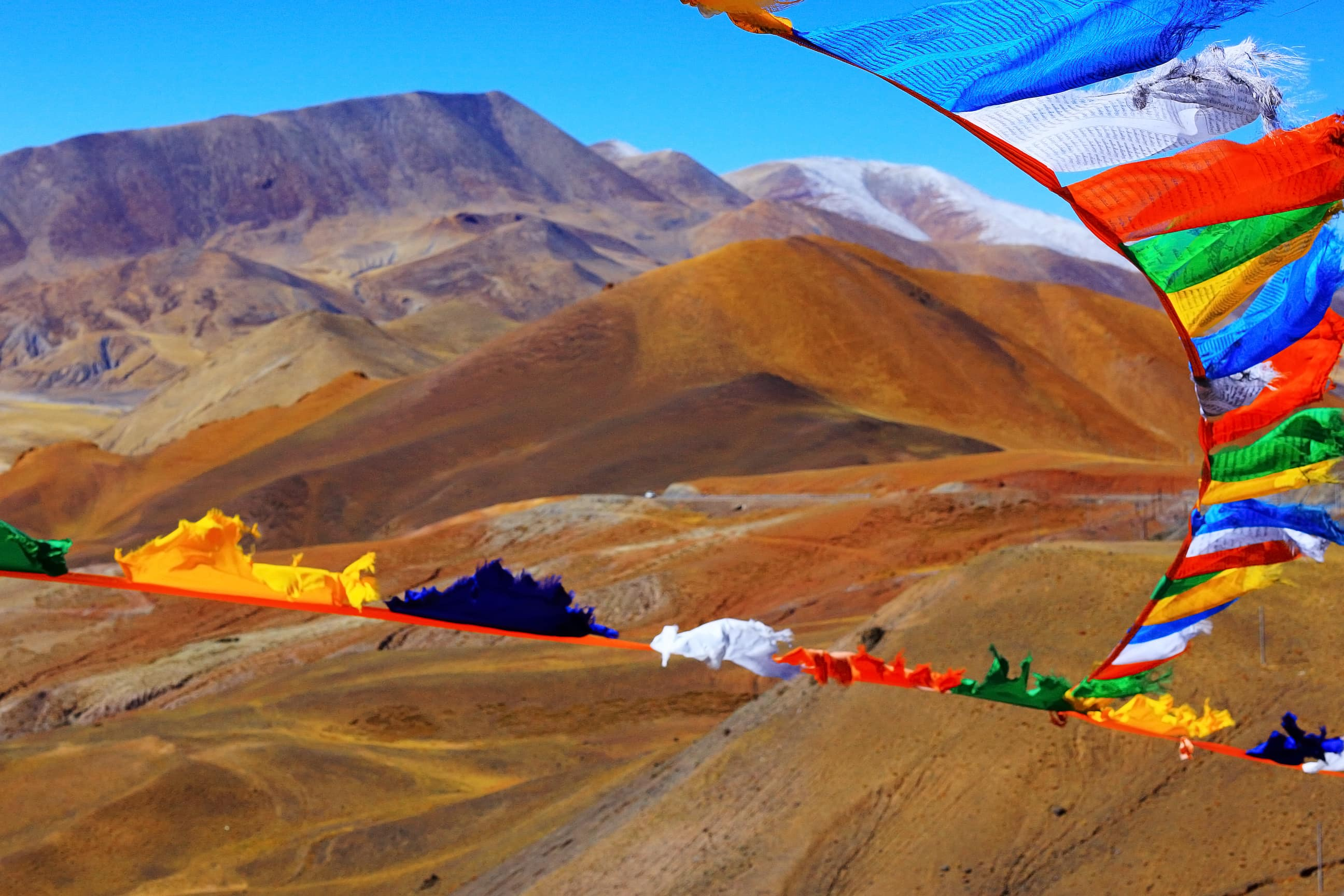 Mountain ranges and prayer flags over high pass in Tibet
