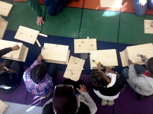 Students learn to use hammers to create their wooden planter boxes