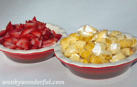 two red dishes filled with chopped strawberries and chopped Twinkies