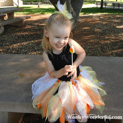 little girl smiling while holding a candy corn lollipop